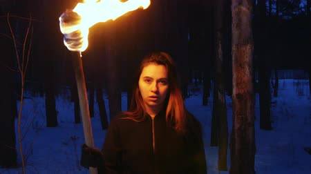 chamas : A beautiful woman with torch walking to a camera in winter forest