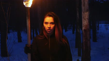chamas : A pretty woman with torch walking to a camera in winter forest