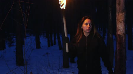 atmosféra : Young scared woman with torch running from something and looking in the camera