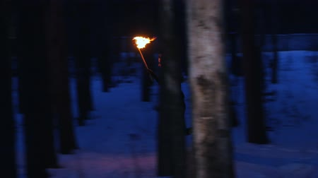 chamas : Young scared woman with torch running from something in the night forest