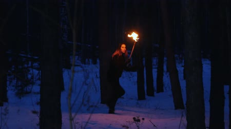 chamas : Young scared woman with torch walking away from something in the night forest