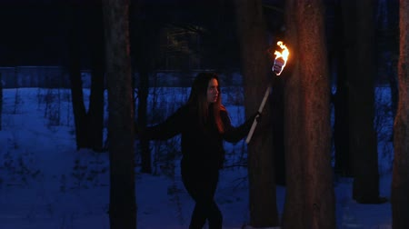 chamas : Young scared woman with torch walking outdoors Vídeos