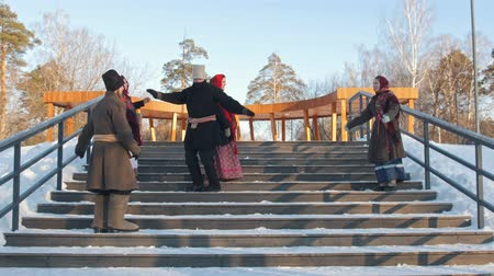 festividades : Russian folk - people in traditional Russian clothes are dancing on the stairs in winter