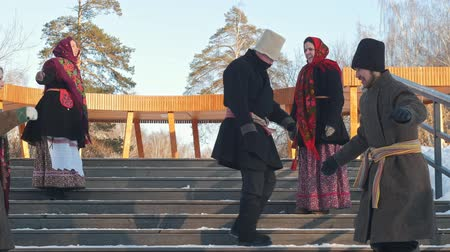 festividades : Russian folk - men and women in traditional Russian clothes are dancing on the stairs in winter