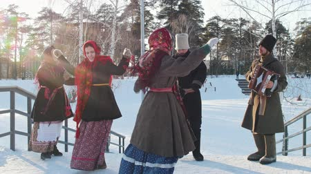 ритуал : Russian folk - men and women in traditional Russian clothes are dancing to the accordion n the park