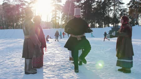 symbol : Russian folk - man is dancing traditional dance in a circle of women in winter
