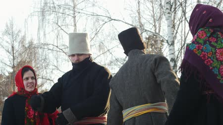 festividades : Russian folk - men are dancing traditional dance in a circle of women in winter