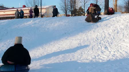 festividades : Russian folk - men and women in Russian folk costumes are riding a snow slide
