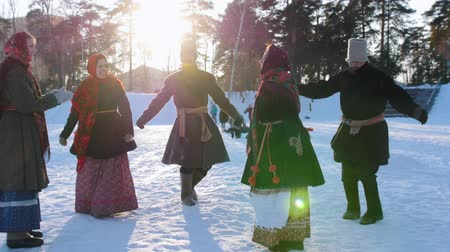 festividades : Russian folk - men and women in Russian folk costumes are dancing in pairs in a winter park