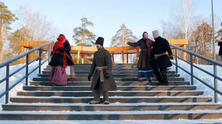 торжества : Russian folk - men and women in felt boots are dancing on the stairs in the winter park
