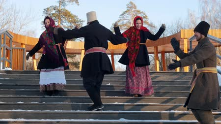торжества : Russian folk - men and women in felt boots are dancing on the stairs in the park Стоковые видеозаписи