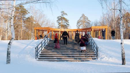 festividades : Russian folk - men and women in felt boots are actively dancing on the stairs in the park