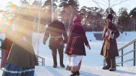 festividades : Russian folk - women in bright scarves are dancing with men on the stairs in the winter park