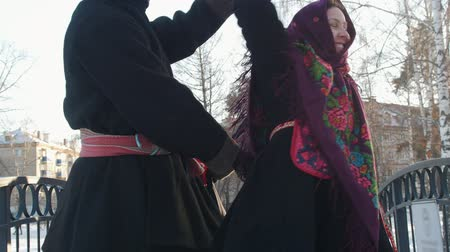 festividades : Russian folk - man and woman in traditional Russian costumes are dancing on the bridge in winter Vídeos