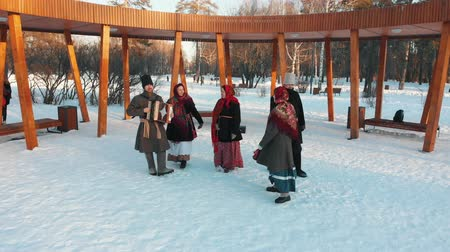 festividades : Russian folklore - russian people in costumes are dancing in the snow park Vídeos