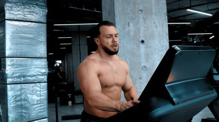 schouder : A bearded attractive man bodybuilder running on the treadmill and changing changes modes