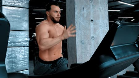 リフト : An attractive man bodybuilder running on the treadmill and changing changes modes