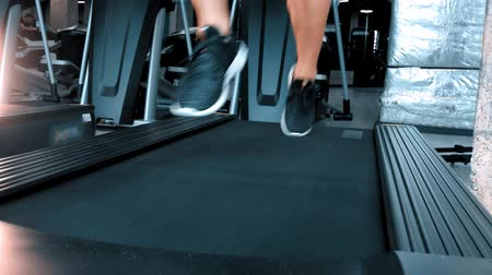 ginásio : A man in sneakers running on the treadmill in the sports gym Stock Footage