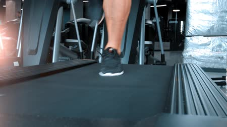 подъемник : A man in sneakers running on the treadmill in the modern sports gym