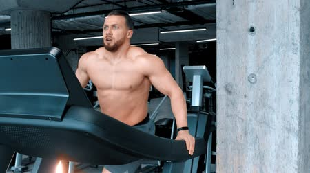 epaule : A bearded attractive young man bodybuilder running on the treadmill with an effort