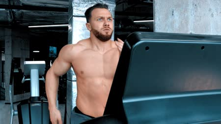 cabeça e ombros : An attractive young man bodybuilder running on the treadmill with an effort in the modern gym