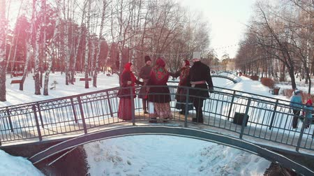 symbol : Russian folklore - people in Russian costumes are dancing on the bridge