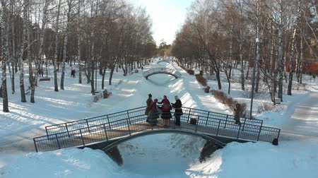 symbol : Russian folklore - five people in russian costumes are dancing on the bridge in winter park