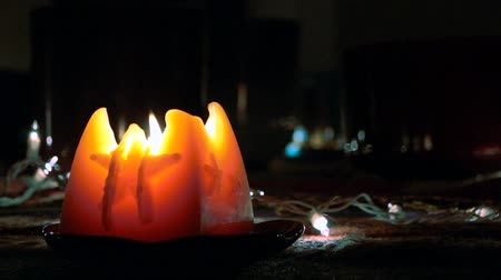 освещенный : A large glowing flickering lit candle on the left creating a magical atmosphere surrounded by dark space on top and right side providing room for text, credits, images or other inserts.
