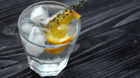 ginástico : Cocktail with citrus fruits, sprig of rosemary and cubes of ice on dark wooden table. Slow camera tilt down Stock Footage