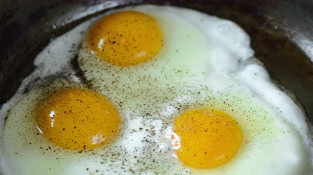 seethe : Cooking Fried eggs. Process of Preparation of Three Fried Egg. Time Lapse. Top view. Full Cycle of Frying Eggs: Break Eggs into a Hot Frying Pan, Salt, Pepper, Remove Eggs from a Frying Pan