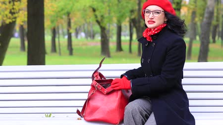 путаница : Beautiful woman with a bag, sitting on bench in autumn park. Стоковые видеозаписи