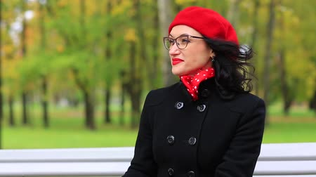 preocupações : Woman in a red beret and glasses sitting in the autumn Park