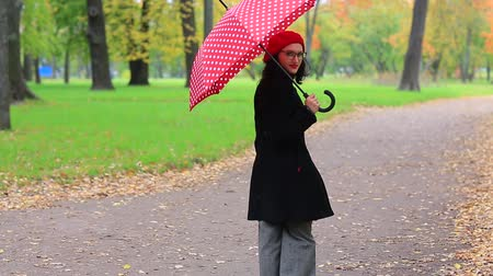 мысли : woman with red umbrella in the autumn Park. Стоковые видеозаписи