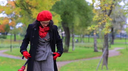 a woman unbuttons her coat in the autumn park Stock Footage