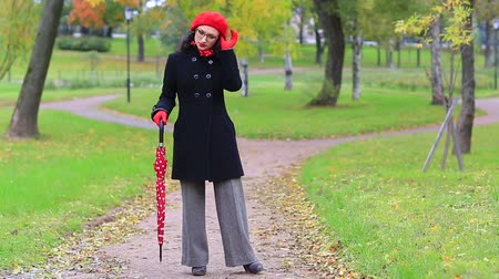 Woman with red umbrella in the autumn park