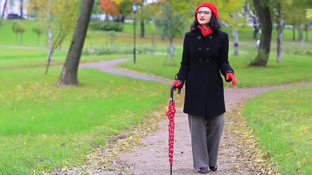 Woman dancing with red umbrella in the autumn park