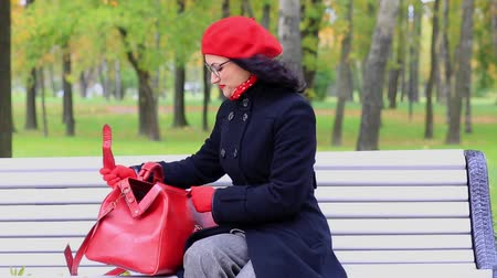 Woman looking something in red bag, on bench in autumn park. teachers day
