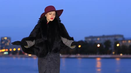 nightcity : Amazing woman in a red hat on the background of the river and the city at night Stock Footage