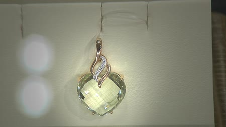 richness : Golden pendant with diamond in a heart shape. Key Light