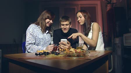 daireler : The young man and two young girls sitting in the kitchen in the evening and look at smartphone. Stok Video