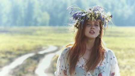 be sad : Walk in the field. A beautiful red-haired girl with a wreath on her head running on a close up, stands and looks out into the distance. She is sad. Slow motion.