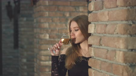 eleganckie : A beautiful girl is in a wine cellar. Slow motion. A serious girl with a glass of champagne.