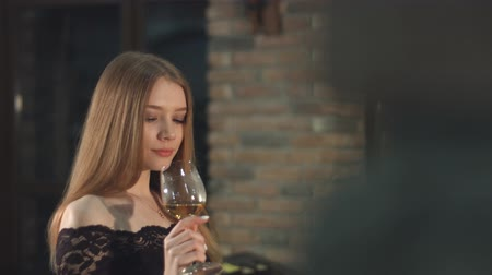 tasting : A beautiful girl is drinking wine. Slow motion. A pretty girl tasting white wine in a wine cellar and smiles.