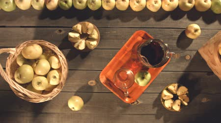 pitcher : Apple juice and apples on the table. Top view. The smooth glide of the camera (from right to left) over the table on which is an apple juice and apples.