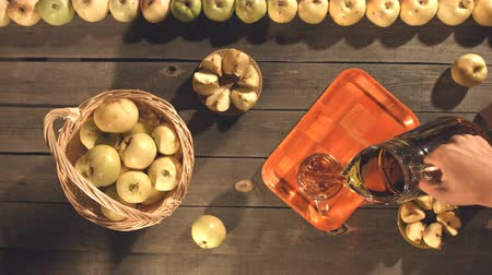 glass pitcher : Apple juice and apples on the table. Top view. Slow motion. A mens hand takes a jug from the table and pours a juice into a mug. The smooth glide of the camera (from left to right) over the table on which is an apple juice and apples. Stock Footage