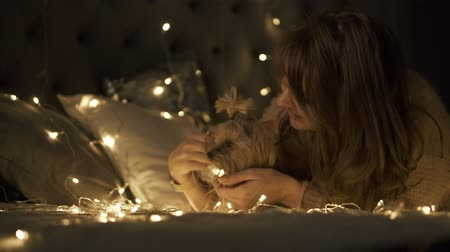 Young girl with dog Yorkshire Terrier surrounded Christmas light in the Christmas decorated room.