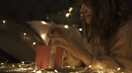 Close up of young happy woman taking her Christmas present in the Christmas decorated room. Christmas lights surround her. Pan Up Stock mozgókép