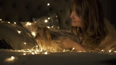 Cute curly hair woman playing with her dog in a warm cozy Christmas room at home