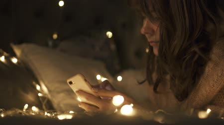 Woman in Christmas decorated room lies on the bed with the phone. Warm Bokeh background , writing sms Stock mozgókép