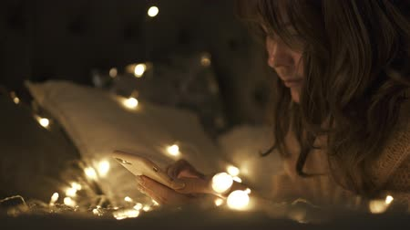 безделушка : Young woman lies on the bed with the phone on the Christmas lights background , chat with her family Стоковые видеозаписи